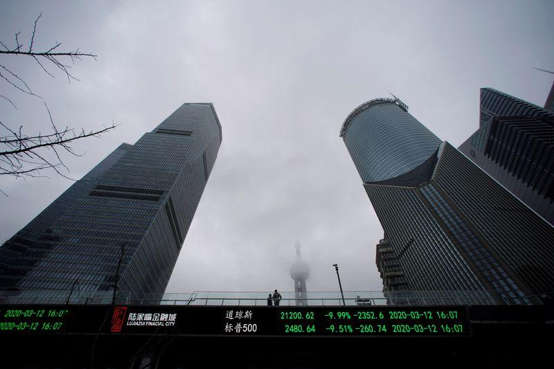 © Reuters. FOTO DE ARCHIVO: Se puede ver a las personas en un puente peatonal con una placa electrónica que muestra los índices Dow Jones y S & P 500 después del brote del nuevo virus corona en el distrito financiero de Lujiazui en Shanghai