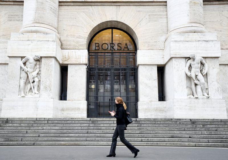 © Reuters. Un passante davanti alla Borsa italiana di Milano