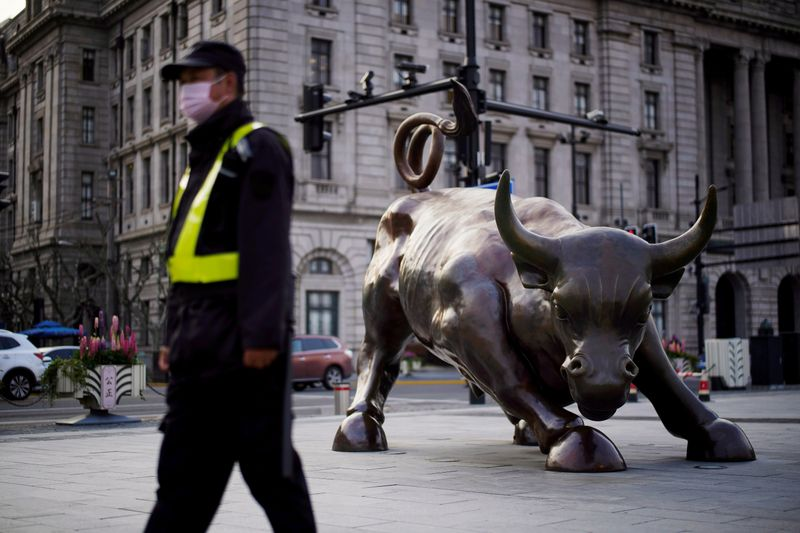 © Reuters. FILE PHOTO: Security guard wearing a face mask walks past the Bund Financial Bull statue on The Bund in Shanghai