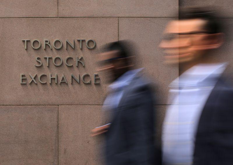 © Reuters. Businessmen pass the Toronto Stock Exchange sing in Toronto
