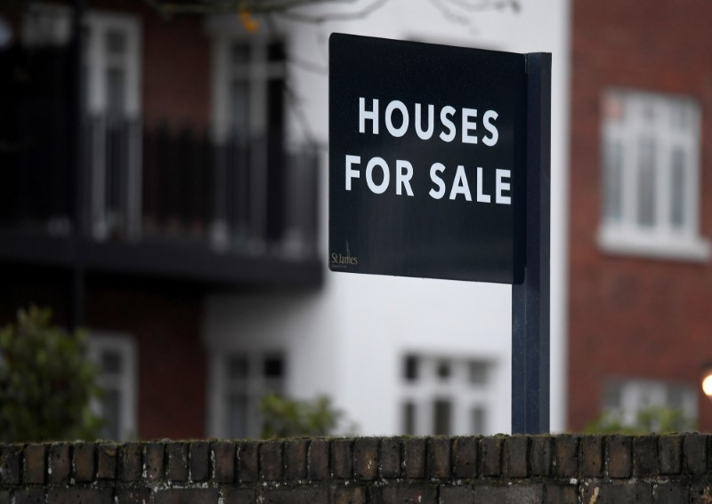 © Reuters. FILE PHOTO: Property sale signs are seen outside of a group of newly built houses in west London