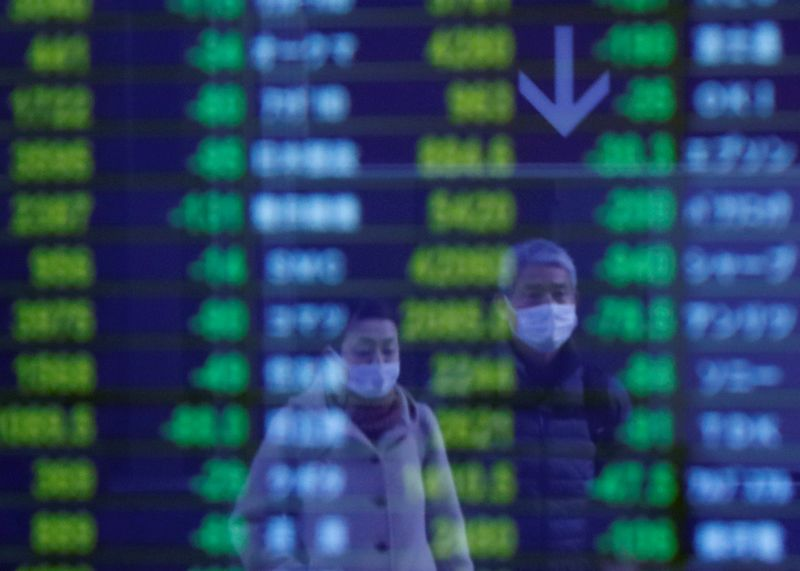 © Reuters. Passersby wearing protective masks, following a coronavirus outbreak, are reflected on a screen showing stock prices outside of a brokerage firm in Tokyo