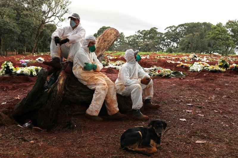 © Reuters. Agentes sepultadores com trajes de proteção durante pandemia de Covid-19 no cemitério de Vila Formosa, em São Paulo