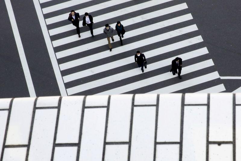 © Reuters. FOTO DE ARCHIVO: Gente cruzando una calle en un distrito comercial de Tokio
