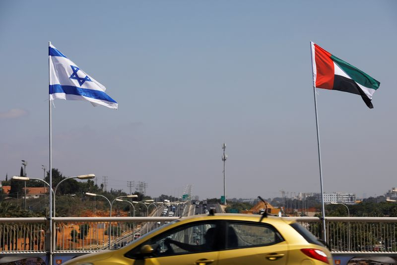 © Reuters. FILE PHOTO: A car drives near the national flags of Israel and the United Arab Emirates as they flutter along a highway following the agreement to formalize ties between the two countries, in Netanya