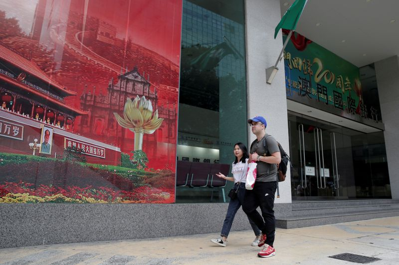 © Reuters. FILE PHOTO: People walk past the headquarters building of Luso International Banking Ltd. in Macau