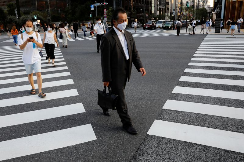 © Reuters. People wearing protective masks make their way at a business district in Tokyo