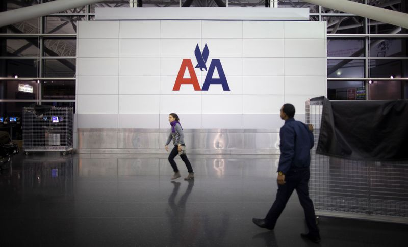 © Reuters. FILE PHOTO: People walk past an American Airlines logo at John F. Kennedy (JFK) airport in in New York