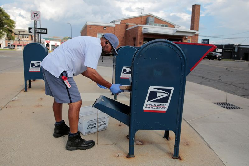© Reuters. A United States Postal Service (USPS) worker handles the mail in a drop-off box