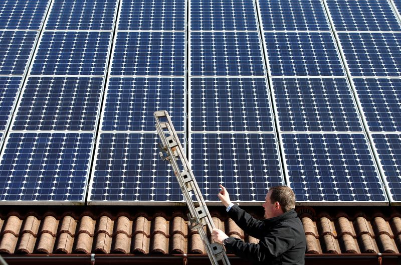 © Reuters. FILE PHOTO: Michael Greif controls his 56 photovoltaic (solar) panels at the roof of his house in Coburg