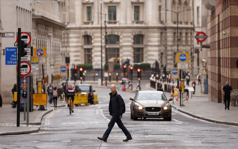 © Reuters. A man crosses the road in the City of London financial district amid the outbreak of the coronavirus disease (COVID-19)