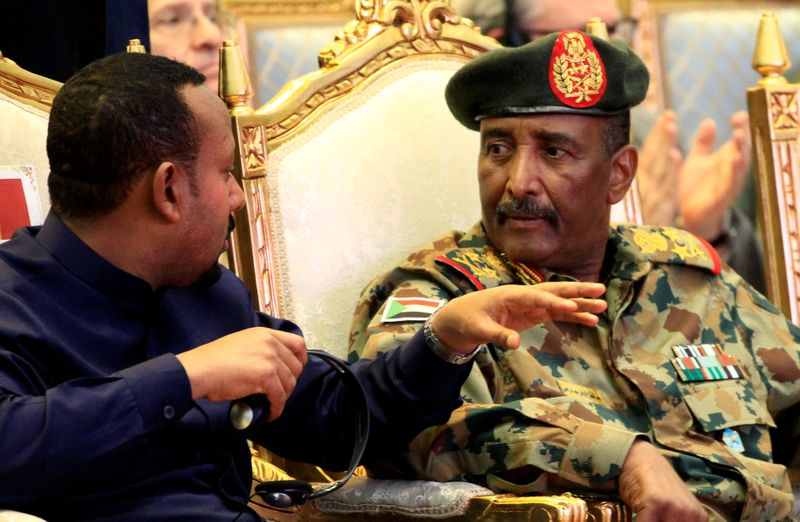 © Reuters. FILE PHOTO: Sudan's Head Of Transitional Military Council, Lieutenant General Abdel Fattah Al-Burhan, listens to Ethiopia's Prime Minister Abiy Ahmed during the signing of the power sharing deal, in Khartoum